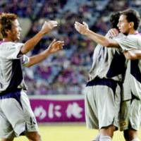 Antlers midfielder Fabio Santos (far right) celebrates with teammates after scoring the game's first goal in the 33rd minute against Cerezo Osaka at Nagai Stadium on Saturday night. The game ended in a 1-1 draw. | KYODO PHOTO