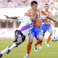 Kyoto Purple Sanga forward Paulinho, left, battles for the ball with Albirex Niigata defender Kazuhiro Chiba in the second half in Saturday's game at Niigata Stadium. The game ended in a 1-1 draw. | KYODO PHOTO