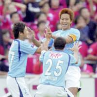 Jubilo Iwata midfielder Takashi Fukunishi (right) is congratulated by teammates after scoring a goal in the 52nd minute during the J. League first-division match against Urawa Reds on Saturday at Yamaha Stadium. Jubilo won 3-2. | KYODO PHOTO