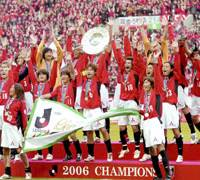 Urawa captain Nobuhisa Yamada lifts the championship shield while surrounded by his teammates after the Reds beat Gamba Osaka 3-2 at Saitama Stadium on the final day of the season Saturday to clinch their first-ever J. League championship. | KYODO PHOTO