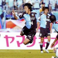 Kawasaki Midfielder Kengo Nakamura (14) falls down after taking a tackle from a Gamba Osaka player in the first half in the J. League Nabisco Cup final at Tokyo's National Stadium on Saturday afternoon. Gamba edged Frontale 1-0 for its first Cup title before a crowd of 41,569. | KYODO PHOTO