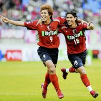 Kashima forward Marquinhos (right) reacts with teammate Yuzo Tashiro after scoring a goal in the 59th minute against Shimizu at Kashima Stadium on Saturday afternoon. With a 3-0 win over S-Pulse, Antlers clinched their first league title in six years. | KYODO PHOTO