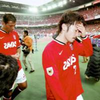 Reds' Yuki Abe (right) and Washington mourn while going back to the locker room after Urawa failed to clinch the J. League championship at Nissan Stadium in Yokohama on Saturday. | KYODO PHOTO