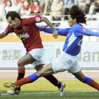 Reds forward Naohiro Takahara (left) dribbles past Yokohama defender Yuji Nakazawa in second-half action at Nissan Stadium in Saturday's J. League Opening Day. Watched by 61,246 spectators, host F. Marinos beat Urawa 1-0. | KYODO PHOTO