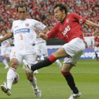 Passing through: Urawa Reds forward Naohiro Takahara (right) passes the ball through Omiya Ardija defender Leandro's legs during their J. Leauge match on Sunday at Saitama Stadium 2002. The match ended in a scoreless draw. | KYODO PHOTO