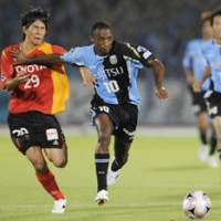 Eyes on the prize: Kawasaki Frontale striker Juninho holds off Nagoya Grampus' Yoshizumi Ogawa at Todoroki Stadium, Kawasaki, on Saturday night. The match ended 1-1. | KYODO PHOTO