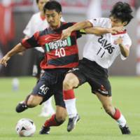 Charged up: Kashima Antlers midfielder Mitsuo Ogasawara tussles for the ball with Urawa Reds striker Tatsuya Tanaka on Sunday night. The match was interrupted by a first-half thunderstorm, but both players scored as play resumed, ending in a 1-1 draw. | KYODO PHOTO
