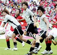 Just missed it: A shoot by Oita Trinita forward Yasuhito Morishima (left), who tries to head in a free kick, hits the goal post and bounces back during Saturday's J. League first-division match against Urawa Reds at Saitama Stadium 2002. The match ended in a scoreless draw. | KYODO PHOTO