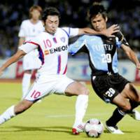That's my ball: FC Tokyo Yohei Kajiyama battles Kawasaki Frontale midfielder Hiroyuki Taniguchi for the ball during a J. League first-division match on Saturday at Todoroki Stadium. FC Tokyo won 1-0. | KYODO PHOTO