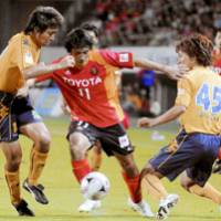 Two on one: Nagoya Grampus forward Keiji Tamada (center) fights JEF United Chiba defenders Tomonobu Hayakawa (right) and Shohei Ikeda for control of the ball during their J. League match on Tuesday at Fukuda Denshi Arena. JEF United won 2-1. | KYODO PHOTO