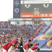 Apologizing to the fans: Disappointed Urawa Reds players bow to the fans after a 2-1 loss to Shimizu S-Pulse on Sunday at Saitama Stadium 2002 in a J. League first-division match. The loss killed Reds' hopes for the championship. | KYODO PHOTO