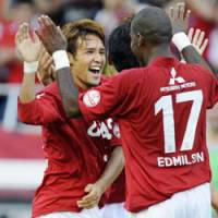 Beaming smiles: Reds defender Hajime Hosogai (left) exchanges high-fives with teammate Edmilson after his goal in the second half of Sunday's game against Montedio Yamagata. Urawa won 4-1. | KYODO PHOTO