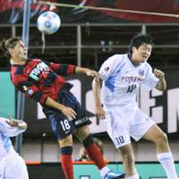 Up in the air: Kashima Antlers forward Marquinhos (left) fights Kawasaki Frontale defender Tomonobu Yokoyama for the ball in the air on Wednesday at Kashima Stadium. Frontale won 3-2. | KYODO PHOTO