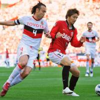 Back in action: Nagoya Grampus defender Marcus Tulio Tanaka (left) and Urawa Reds defender Mitsuru Nagata vie for the ball in Sunday's game, the teams' first J.?League action since the March 11 earthquake. | KYODO