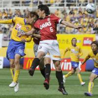 Rising to the occasion: Sendai forward Yoshiaki Ota (left) scores a goal, moving past Reds midfielder Nobuhisa Yamada in the 40th minute on Friday. Vegalta defeated Urawa 1-0 in their first game at home since the March 11 earthquake.   KYODO PHOTO