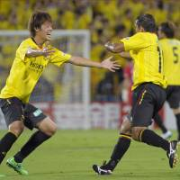 No holding back: Reysol's Hiroki Sakai, left, celebrates with teammate Leandro Domingues after Leandro's tying goal against Sanfrecce on Wednesday night. Reysol won 3-1. | KYODO