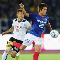 Heat of the night: Marinos midfielder Hiroyuki Taniguchi (right) and Vissel defender Junya Tanaka compete for the ball in first-half action on Saturday at Nissan Stadium. | KYODO PHOTO