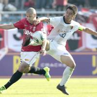 Tangled up: Kashima's Mitsuo Ogasawara (right) fights for the ball with Urawa's Sergio Escudero during the Nabisco Cup final at National Stadium on Saturday. Kashima won 1-0 after extra time. | KYODO PHOTO