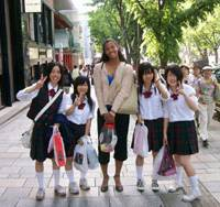 Ree Browne, a former California State University-Dominguez Hills women's basketball player, poses for a photo with Japanese students during a recent visit to Nagoya. Browne has signed a contract to play for the WJBL's Mitsubishi Koalas, who begin preseason training camp on Tuesday. | CSUDH SPORTS INFORMATION PHOTO