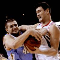 Up close and personal: Denver's Linas Kleiza (left) and Houston's Yao Ming wrestle for the ball during the Rockets' 108-96 win on Tuesday.   AP PHOTO