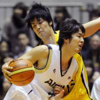 Brothers in arms: Kosuke Takeuchi (with ball) takes on twin brother Joji in the Emperor's Cup final on Monday. | KYODO PHOTO