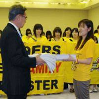 Tohoku spirit personified: Commissioner Toshimitsu Kawachi (left) receives a stack of signed petitions from an 89ers fan on May 21 at Ariake Colosseum. Boosters collected 20,000 signatures to symbolize their hope that the team would return to the league for the 2011-12 season. | KYODO PHOTO