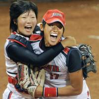 Japan pitcher Yukiko Ueno and catcher Yukiyo Mine celebrate after defeating the U.S. in the gold medal softball game.