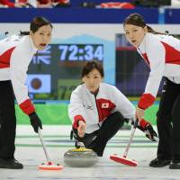 Big victory: Kotomi Ishizaki delivers the stone as teammates Anna Ohmiya (left) and Mari Motohashi look on during the first end against Great Britain on Friday. Japan won 11-4. | KYODO PHOTO