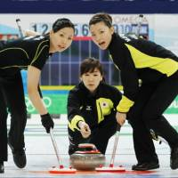 Slipping away: Kotomi Ishizaki (center) delivers the stone while Mari Motohashi (right) and Anna Ohmiya sweep during the first end against Switzerland on Monday. | KYODO PHOTO