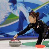 Turned to stone: Mari Motohashi delivers a stone during Japan's 10-6 curling defeat to Sweden on Tuesday. The loss eliminated Japan from the competition. | AP PHOTO