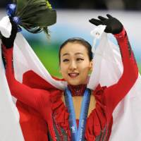 Silver medalist: Mao Asada waves to the crowd after receiving her medal for finishing second in the women's figure skating competition at the Vancouver Olympics on Thursday.   KYODO PHOTO