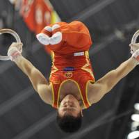 Ring king: Chen Yibing, a three-time world rings champion, performs up to his usual high standards at the world gymnastics championships in Tokyo, but his team fell behind in overall standings, with the Japan men's team taking the lead on Monday.   KYODO PHOTO