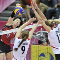 Tough defense: Japan's Mizuho Ishida tries to spike the ball past Germany's Corina Ssuschke-Voigt and Margaret Kozuch during Friday's FIVB World Grand Prix women's volleyball match in Osaka. | KYODO