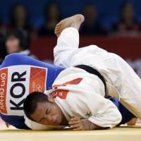 Web of confusion: Masashi Ebinuma (in white) competes against South Korea's Cho Jun Ho in the quarterfinals of the men's 66-kg Olympic judo competition on Sunday. | AP