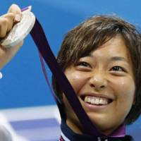 Satomi Suzuki proudly holds her silver medal aloft Thursday for the women's 200-meter breaststroke. | KYODO