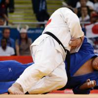 Another one bites the dust: Ihar Makarau of Belarus (in white) competes with Daiki Kamikawa during the over-100-kg judo competition at the London Olympics on Friday. | AP