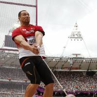 Solid start: Koji Murofushi competes in the qualifying round of the men's hammer throw on Friday at the Olympic Stadium. | AP