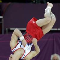 Upside down: Kohei Uchimura competes in the men's floor exercise final on Sunday. Uchimura finished second behind China's Zou Kai. | KYODO