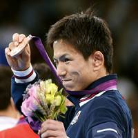 Shinichi Yumoto shows off his bronze medal in the men's 55-kilogram freestyle wrestling. | KYODO