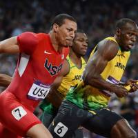 Catch you later: Usain Bolt runs ahead of Ryan Bailey during the men's 4x100-meter relay final on Saturday. | AFP-JIJI