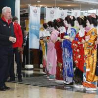 Warm welcome: International Olympic Committee Vice President Craig Reedie of Britain (second from left) is greeted by kimono-clad models as he visits the Big Sight in Tokyo on Wednesday.   AP