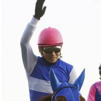 Scarlet Pimpernel: Jockey Katsumi Ando waves atop Daiwa Scarlet after the filly won the Arima Kinen on Sunday. | KYODO PHOTO
