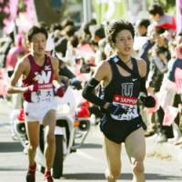 Going for the victory: Toyo University's Yu Chiba (right) takes off, leaving Kenji Nakajima of Waseda University behind during the eighth leg of the Tokyo-Hakone Collegiate Ekiden Road Relay on Saturday. Toyo clinched its first title. | KYODO PHOTO