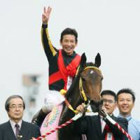 Time to celebrate: Jockey Katsumi Andoh salutes the crowd after riding Buena Vista to a victory in the 70th running of the Oaks on Sunday at Tokyo Racecourse. | KYODO PHOTO