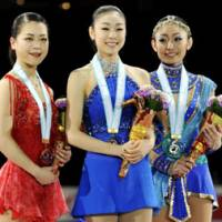 Standing proud: Kim Yu Na (center), the women's Grand Prix Final champion, silver medalist Miki Ando (right) and third-place finisher Akiko Suzuki share the spotlight on Saturday evening at Yoyogi National Gymnasium. | KYODO PHOTO