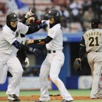 Can't shut the door: Fighters closer Hisashi Takeda looks away as Lotte's Shoitsu Omatsu, left, and Tsuyoshi Nishioka celebrate during the ninth inning of their game on Sunday. | KYODO PHOTO