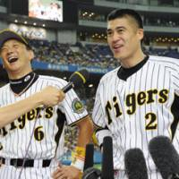 All smiles: Tomoaki Kanemoto (left), Kenji Johjima and the Hanshin Tigers will begin a critical week in the Central League atop the standings. | AP PHOTO