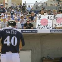 Come together: Milwaukee Brewers reliever and Sendai native Takashi Saito walks off the field as a fan holds up a sign of support for the Tohoku region on Sunday in Maryvale, Ariz. Saito's wife and three daughters are safe. | KYODO PHOTO