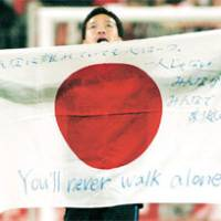 Stand together: Yuto Nagatomo holds up a Japanese flag bearing a message of solidarity after Inter Milan's Champions League over Bayern Munich last week. | KYODO PHOTO