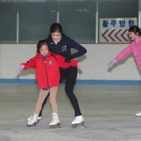 Heart of gold: Olympic champion Kim Yu Na gives instruction to a Special Olympian at Seoul's Dongehun Indoor Ice Skating Rink last Friday. | COURTESY SPECIAL OLYMPICS